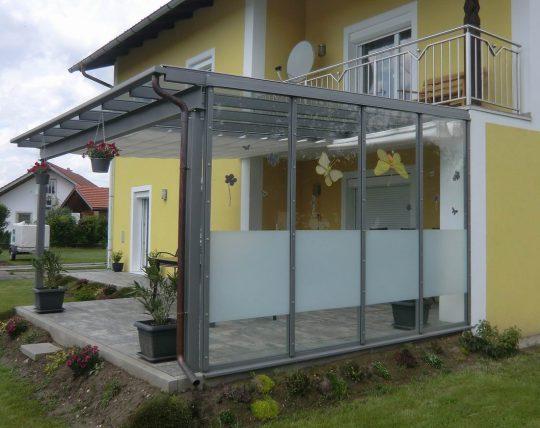 Terrassendach Aschau im Chiemgau, mit Seitenvergalsung als Windschutz und mehrteiligem Sonnenschutz.
