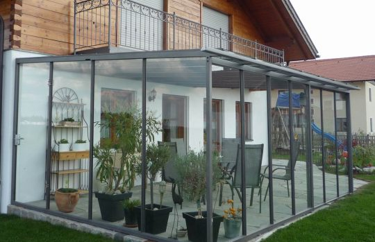 Terrassenüberdachung in Rosenheim, mit Seitenverglasung und Windschutz vorne. Privatkunde in Rosenheim