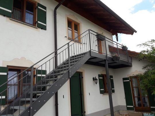 Stahltreppe in Rosenheim, verzinkt und pulverbeschichtet mit Gitterroststufen und Stegkonstruktion als Übergangspodest. Geländer im Landhausstil, mit dezent geschmiedeten Füllstäben.
