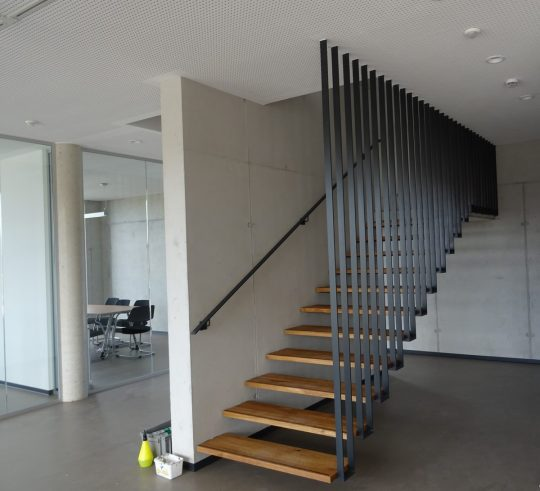 Harfentreppe in Traunstein, mit Deckenabhängung als Flachstahlgeländer und Wandhandlauf.